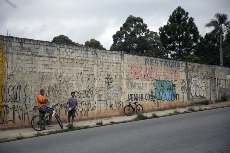 Boys wait on the roadside in the poor neighbourhood of Itaquera, adjacent to the 'Arena de Sao Paulo' stadium, on June 21, 2014 in Sao Paulo, Brazil. The Arena de Sao Paulo, which is reported to have cost in excess of 200 million GBP, hosted the opening match of the 2014 FIFA World Cup and has a capacity of over 61,000. The total cost borne by Brazil for staging the 2014 World Cup is estimated to be 6.5 billion GBP, which critics have argued would have better spent on the millions of Brazilians living in poverty. (Photo by Oli Scarff/Getty Images)