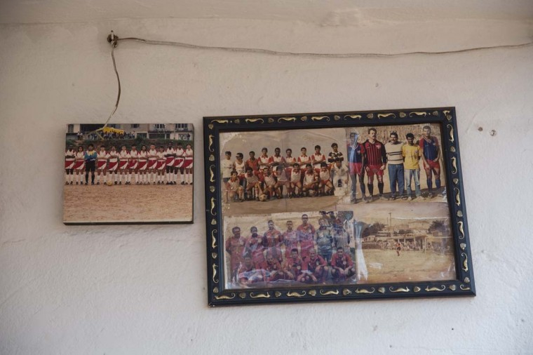 Faded team photographs adorn the walls of the 'Artur Alvim' football club's office in the poor neighbourhood of Itaquera, adjacent to the 'Arena de Sao Paulo' stadium, on June 21, 2014 in Sao Paulo, Brazil. The Arena de Sao Paulo, which is reported to have cost in excess of 200 million GBP, hosted the opening match of the 2014 FIFA World Cup and has a capacity of over 61,000. The total cost borne by Brazil for staging the 2014 World Cup is estimated to be 6.5 billion GBP, which critics have argued would have better spent on the millions of Brazilians living in poverty. (Photo by Oli Scarff/Getty Images)