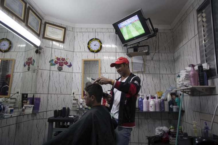 A television shows a World Cup match in a barber shop in the poor neighbourhood of Itaquera, adjacent to the 'Arena de Sao Paulo' stadium, on June 21, 2014 in Sao Paulo, Brazil. The Arena de Sao Paulo, which is reported to have cost in excess of 200 million GBP, hosted the opening match of the 2014 FIFA World Cup and has a capacity of over 61,000. The total cost borne by Brazil for staging the 2014 World Cup is estimated to be 6.5 billion GBP, which critics have argued would have better spent on the millions of Brazilians living in poverty. (Photo by Oli Scarff/Getty Images)