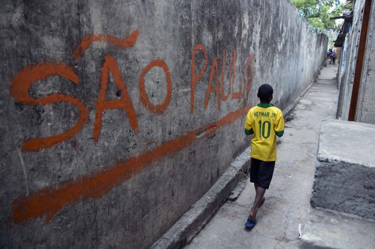 A boy wearing a Brazilian football shirt walks through the narrow streets of the poor neighbourhood of Itaquera, adjacent to the 'Arena de Sao Paulo' stadium, on June 21, 2014 in Sao Paulo, Brazil. The Arena de Sao Paulo, which is reported to have cost in excess of 200 million GBP, hosted the opening match of the 2014 FIFA World Cup and has a capacity of over 61,000. The total cost borne by Brazil for staging the 2014 World Cup is estimated to be 6.5 billion GBP, which critics have argued would have better spent on the millions of Brazilians living in poverty. (Photo by Oli Scarff/Getty Images)