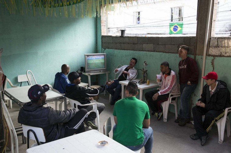 Men watch a television showing a World Cup match in a house in the poor neighbourhood of Itaquera, adjacent to the 'Arena de Sao Paulo' stadium, on June 21, 2014 in Sao Paulo, Brazil. The Arena de Sao Paulo, which is reported to have cost in excess of 200 million GBP, hosted the opening match of the 2014 FIFA World Cup and has a capacity of over 61,000. The total cost borne by Brazil for staging the 2014 World Cup is estimated to be 6.5 billion GBP, which critics have argued would have better spent on the millions of Brazilians living in poverty. (Photo by Oli Scarff/Getty Images)