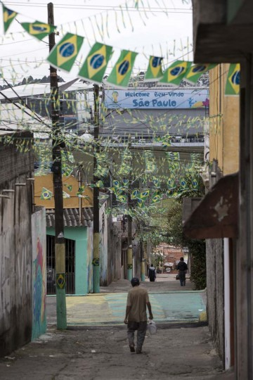 A man walks along a street in the poor neighbourhood of Itaquera towards the 'Arena de Sao Paulo' stadium on June 21, 2014 in Sao Paulo, Brazil. The Arena de Sao Paulo, which is reported to have cost in excess of 200 million GBP, hosted the opening match of the 2014 FIFA World Cup and has a capacity of over 61,000. The total cost borne by Brazil for staging the 2014 World Cup is estimated to be 6.5 billion GBP, which critics have argued would have better spent on the millions of Brazilians living in poverty. (Photo by Oli Scarff/Getty Images)