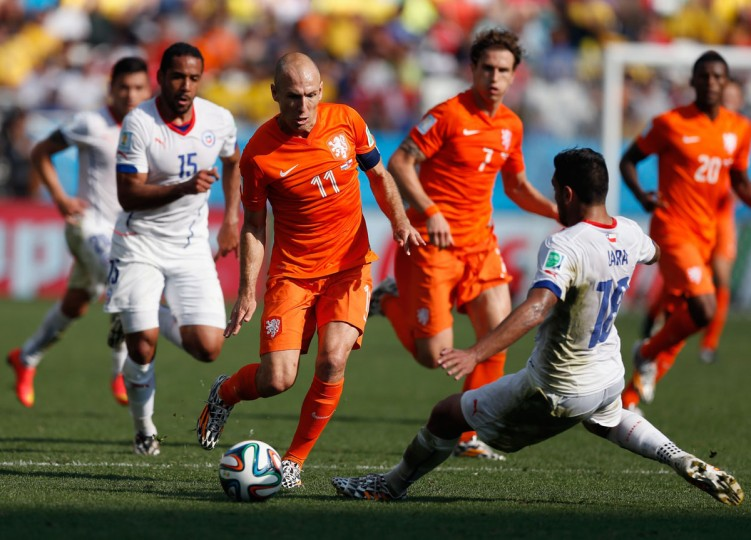 Arjen Robben of the Netherlands controls the ball as Gonzalo Jara of Chile gives chase during the 2014 FIFA World Cup Brazil Group B match between the Netherlands and Chile at Arena de Sao Paulo on June 23, 2014 in Sao Paulo, Brazil. (Photo by Alexandre Schneider/Getty Images)