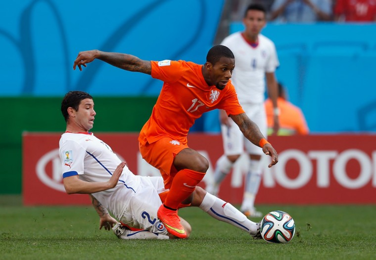 Eugenio Mena of Chile tackles Jeremain Lens of the Netherlands during the 2014 FIFA World Cup Brazil Group B match between the Netherlands and Chile at Arena de Sao Paulo on June 23, 2014 in Sao Paulo, Brazil. (Photo by Alexandre Schneider/Getty Images)