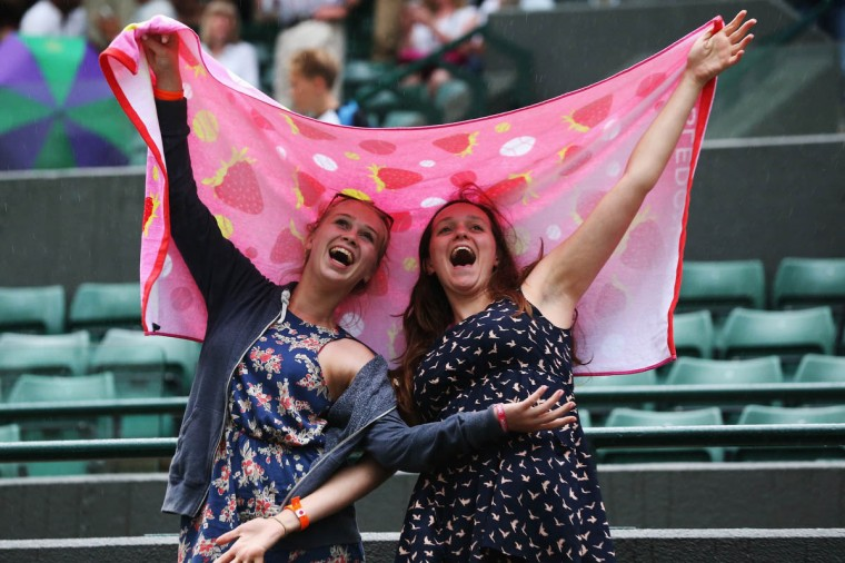 Fans remain in good spirits as rain suspends play on Court One during the Jo-Wilfried Tsonga of France and Jurgen Melzer of Austria singles match on day one of the Wimbledon Lawn Tennis Championships at the All England Lawn Tennis and Croquet Club at Wimbledon. (Steve Bardens/Getty Images)
