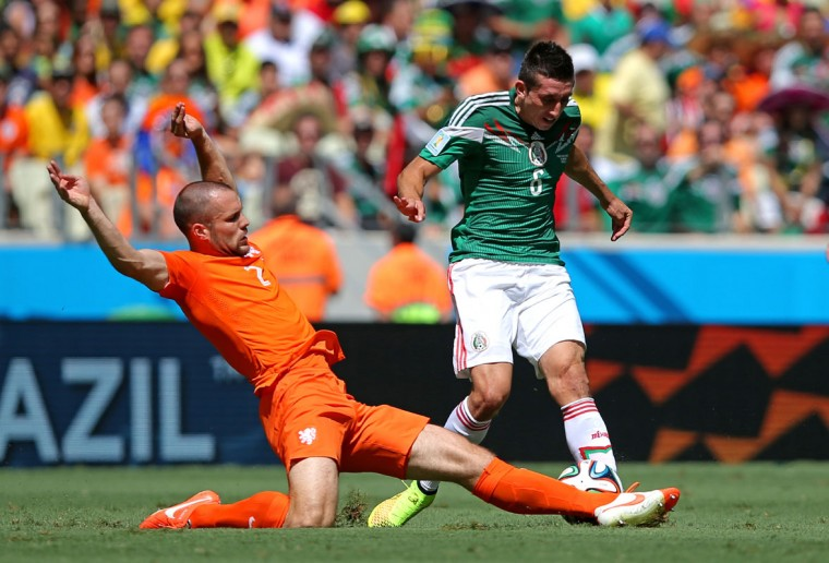 Ron Vlaar of the Netherlands tackles Hector Herrera of Mexico during the 2014 FIFA World Cup Brazil Round of 16 match between Netherlands and Mexico at Castelao on June 29, 2014 in Fortaleza, Brazil. (Dean Mouhtaropoulos/Getty Images)