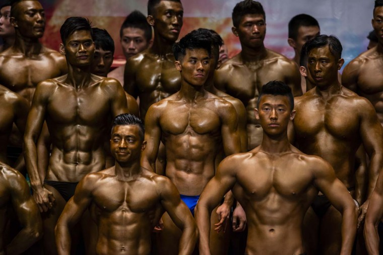 Bodybuilders flex muscles for judges on stage during the Hong Kong Bodybuilding Championship on June 29, 2014 at the Queen Elizabeth Stadium in Hong Kong, Hong Kong. (Victor Fraile/Getty Images)