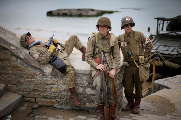 French teenagers who are part of a WWII reenactment group relax on the promenade of Arromanche next to 'Gold Beach'as preparations for the 70th Anniversary Of D-Day are finalised on June 2, 2014 in Arromanches-les-Bains, France. Friday 6th June is the 70th anniversary of the D-Day landings which saw 156,000 troops from the allied countries including the United Kingdom and the United States join forces to launch an audacious attack on the beaches of Normandy, these assaults are credited with the eventual defeat of Nazi Germany. A series of events commemorating the 70th anniversary are planned for the week with many heads of state travelling to the famous beaches to pay their respects to those who lost their lives. (Christopher Furlong/Getty Images)