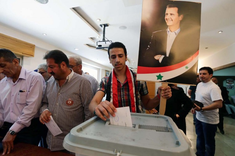 "A Syrian man casts his ballot holding a placard bearing a portrait of current President and candidate Bashar al-Assad during the presidential election on June 3, at a polling station in Damascus. Voting offices opened in Syrian regime-held areas for a presidential election that al-Assad is certain to win, and that has been slammed as a ""farce"" by the opposition.   