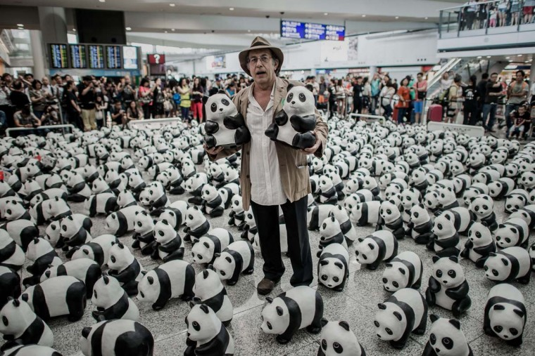 French artist Paulo Grangeon poses with some of his 1,600 papier-mache pandas at Hong Kong's international airport on June 9, 2014 as part of their first appearance in the city. The event, consisting of placing 1,600 papier-mache pandas in various cities around the world, was created by the French artist in collaboration with the WWF and is aimed at raising awareness of the endangered species. (Philippe Lopez/AFP/Getty Images)