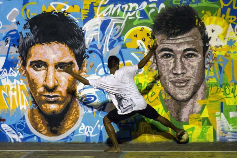 Youngsters play football in front of a mural of Argentine football player Lionel Messi (L) and Brazil's player Neymar da Silva Santos Junior at a field of Tavares Bastos shantytown (favela) in Rio de Janeiro, Brazil on June 8, 2014, just four days ahead of the FIFA World Cup 2014. (Yasuyoshi Chiba/AFP/Getty Images)