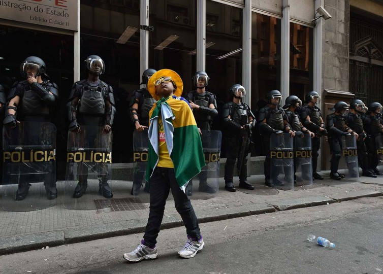 Riot police forces stand guard during a demonstration by striking subway workers and members of the MTST (Homeless Workers' Movement), on June 9, 2014 in Sao Paulo, Brazil. Metro's workers demand 12.2 percent salary raise. The five-day-old strike has already caused massive traffic jams in Brazil's largest city as its new stadium prepares to welcome more than 60,000 fans for June 12 Brazil-Croatia game. (Nelson Almeida/AFP/Getty Images)