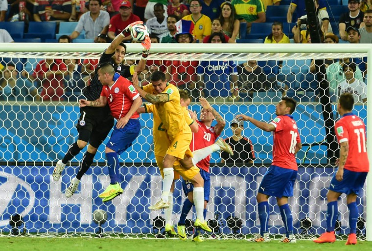 Chile's goalkeeper Claudio Bravo (Left) secures the ball on his goal line during a Group B football match between Chile and Australia at the Pantanal Arena in Cuiaba during the 2014 FIFA World Cup on June 13, 2014. (Martin Bernetti/Getty Images)