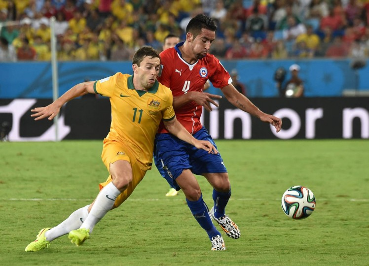 Chile's defender Mauricio Isla (Right) and Australia's forward Tommy Oar vie for the ball during a Group B football match between Chile and Australia at the Pantanal Arena in Cuiaba during the 2014 FIFA World Cup on June 13, 2014. (Luis Acosta/Getty Images)