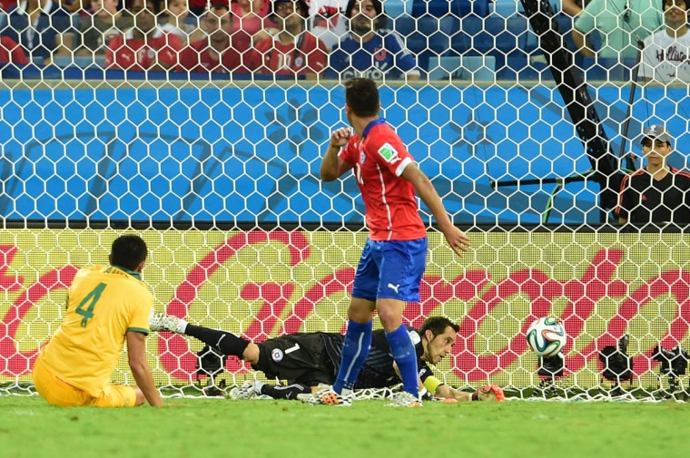 Chile's goalkeeper Claudio Bravo (Below) dives for the ball during a Group B football match between Chile and Australia at the Pantanal Arena in Cuiaba during the 2014 FIFA World Cup on June 13, 2014. (Martin Bernetti/Getty Images)