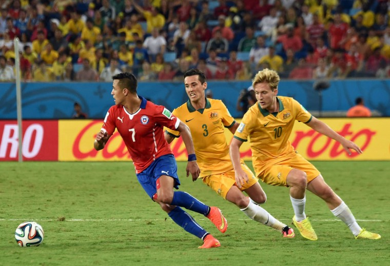 Chile's forward Alexis Sanchez (Left), Australia's defender Jason Davidson (Center) and Australia's forward Ben Halloran (Right) vie for the ball during a Group B football match between Chile and Australia at the Pantanal Arena in Cuiaba during the 2014 FIFA World Cup on June 13, 2014. (Luis Acosta/Getty Images)