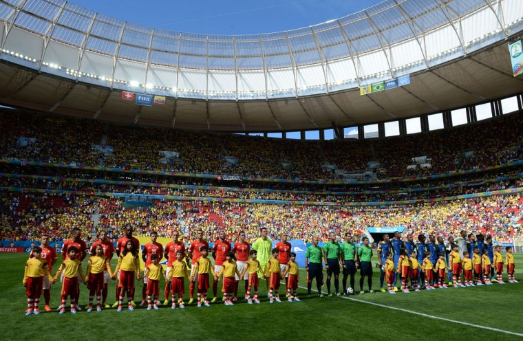 Members of Swiss national team (L) and Ecuadorian team listen to national anthems prior to a Group E football match between Switzerland and Ecuador at the Mane Garrincha National Stadium in Brasilia during the 2014 FIFA World Cup on June 15, 2014. (Anne-Christine Poujoulatanne/AFP/Getty Images)