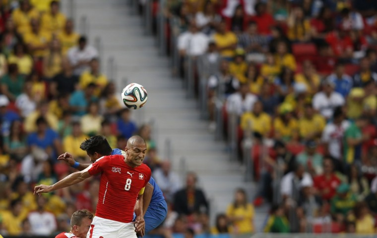 Switzerland's midfielder and captain Goekhan Inler (front) heads the ball during a Group E football match between Switzerland and Ecuador at the Mane Garrincha National Stadium in Brasilia during the 2014 FIFA World Cup on June 15, 2014. (Adrian Dennis/AFP/Getty Images)