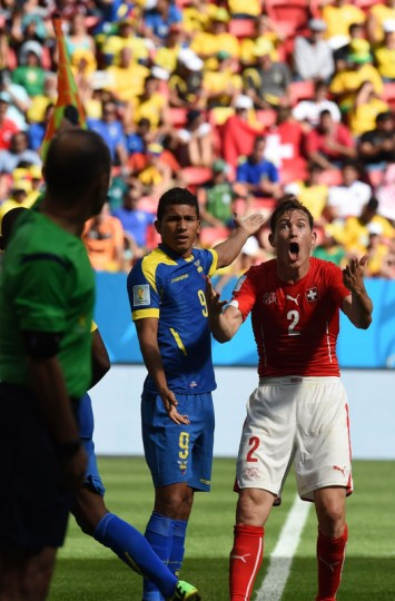 Switzerland's defender Stephan Lichtsteiner (R) reacts past Ecuador's forward Joao Rojas during a Group E football match between Switzerland and Ecuador at the Mane Garrincha National Stadium in Brasilia during the 2014 FIFA World Cup on June 15, 2014. (Pedro Ugarte/AFP/Getty Images)