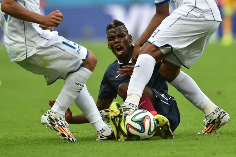 France's midfielder Paul Pogba (down) is tackled by Honduras' midfielder Wilson Palacios (R) during a Group E football match between France and Honduras at the Beira-Rio Stadium in Porto Alegre during the 2014 FIFA World Cup on June 15, 2014. (Rodrigo Arangua/AFP/Getty Images)