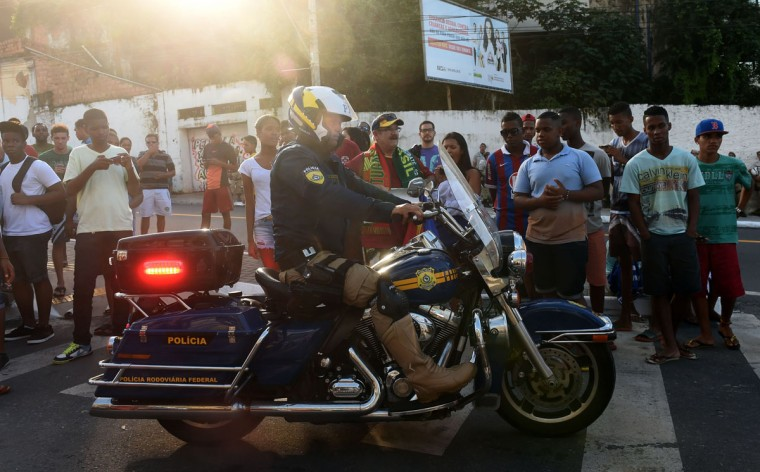 A Brazilian policeman drives a motorbike past fans outside the Fonte Nova Arena in Salvador, where the Portuguese national team are training, as they wait to see Portugal's forward and captain Cristiano Ronaldo on June 15, 2014 on the eve of the Group G football match between Germany and Portugal in the 2014 FIFA World Cup. (PATRIK STOLLARZ/AFP/Getty Images)