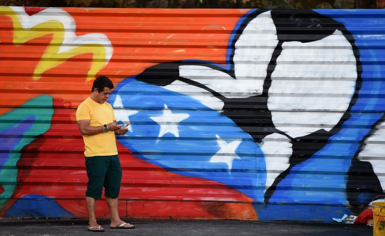 A man stands in front of a mural painting near the Fonte Nova Arena in Salvador on June 15, 2014 on the eve of the Group G football match between Germany and Portugal during the 2014 FIFA Football World Cup in Brazil. (PATRIK STOLLARZ/AFP/Getty Images)