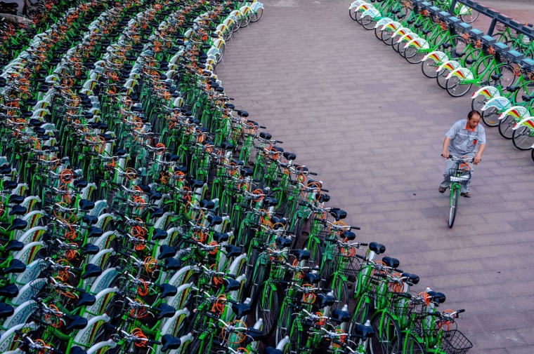 """This picture taken on June 14, 2014 shows a man rising a public bicycle through a bicycle-sharing station in Beijing. Beijing is acutely aware of an increasing number of angry protests over environmental concerns in the country, where three decades of rapid and unfettered industrial expansion have taken a heavy toll. Premier Li Keqiang announced in March that Beijing was """"declaring war"""" against pollution. (AFP/Getty Images)"""
