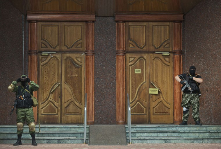 Pro-Russian rebels stand guard outside a local branch of the National Bank of Ukraine after seizing the building in Donetsk, eastern Ukraine, on June 16, 2014. Pro-Russian rebels on June 16 seized the Ukrainian government's central bank building in the eastern separatist stronghold city of Donetsk in a bid to win control over its assets, an AFP correspondent said. (DANIEL MIHAILESCU/AFP/Getty Images)