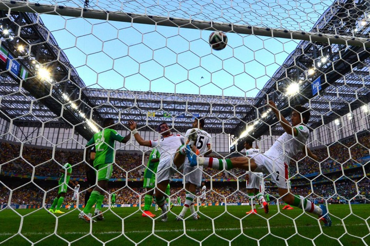 Iran defender Khosro Heidari and midfielder Ehsan Hajsafi (left) kick the ball away from the goal during the Group F football match between Iran and Nigeria at the Baixada Arena in Curitiba during the 2014 FIFA World Cup on June 16, 2014. (LUIS ACOSTA/AFP/Getty Images)