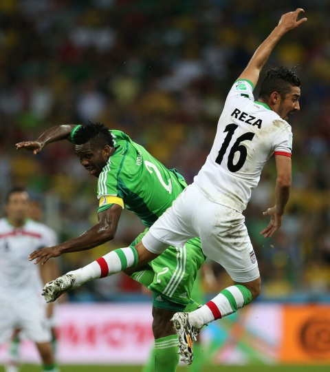 Nigeria's defender Joseph Yobo (left) fights for the ball with Iran's forward Reza Ghoochannejhad during a Group F football match between Iran and Nigeria at the Baixada Arena in Curitiba at the 2014 FIFA World Cup on June 16, 2014. (BEHROUZ MEHRI/AFP/Getty Images)