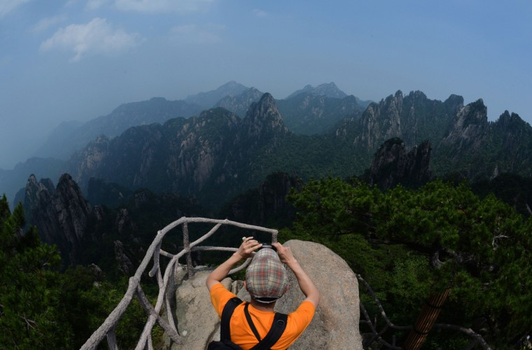 This photo taken on June 15, 2014 shows a tourist viewing granite rock formations at Lion Peak in the Huangshan (Yellow Mountains) park in Anhui Province. The UNESCO World Heritage Site is one of China's major tourist destinations and has been a source of inspiration to Chinese painters, writers and poets for thousands of years. (AFP/Getty Images/Mark Ralston)