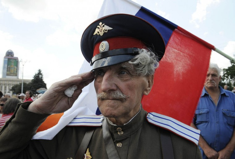 A veteran Cossack salutes in front of Russian flag as pro-Russian militants take the military oath of allegiance to the so-called People's Republik of Donetsk during the ceremony in the centre of the east. (Alexander Khudoteply/Getty Images)