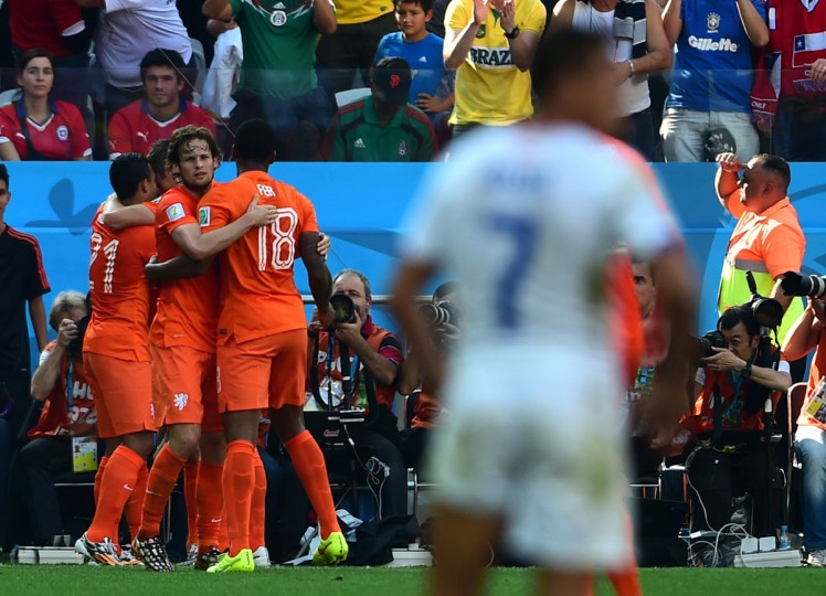 Netherlands forward Memphis Depay (left) celebrates with teammates after scoring to make it 2-0 in a Group B football match between Netherlands and Chile at the Corinthians Arena in Sao Paulo during the 2014 FIFA World Cup on June 23, 2014. Netherlands won 2-0. (MARTIN BERNETTI/AFP/Getty Images)