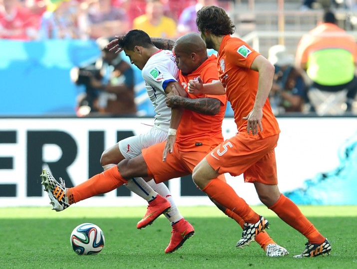 Netherlands midfielder Nigel de Jong (center) tackles Chile forward Alexis Sanchez during a Group B football match between Netherlands and Chile at the Corinthians Arena in Sao Paulo during the 2014 FIFA World Cup on June 23, 2014. Netherlands won 2-0. (MARTIN BERNETTI/AFP/Getty Images)