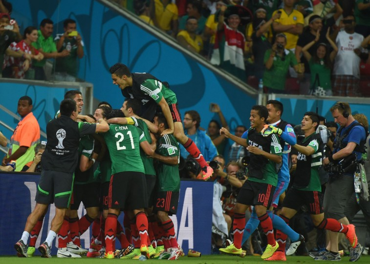 Mexico's players celebrate after scoring during a Group A football match between Croatia and Mexico at the Pernambuco Arena in Recife during the 2014 FIFA World Cup on June 23, 2014. (EMMANUEL DUNAND/AFP/Getty Images)