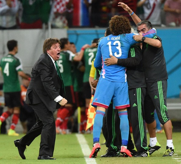 Mexico goalkeeper Guillermo Ochoa (in blue) and Mexico coach Miguel Herrera celebrate a goal by their team during a Group A football match between Croatia and Mexico at the Pernambuco Arena in Recife during the 2014 FIFA World Cup on June 23, 2014. (DIMITAR DILKOFF/AFP/Getty Images)