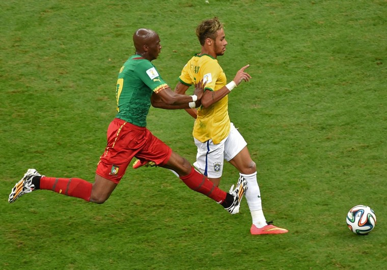 Cameroon midfielder Stephane Mbia (left) and Brazil forward Neymar vie for the ball during a Group A football match at the Mane Garrincha National Stadium in Brasilia during the 2014 FIFA World Cup on June 23, 2014. (EVARISTO SA/AFP/Getty Images)