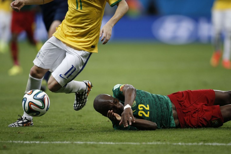 Cameroon defender Allan Nyom (bottom) falls to the ground as he vies for the ball against Brazil's midfielder Oscar during the Group A football match between Cameroon and Brazil at the Mane Garrincha National Stadium in Brasilia during the 2014 FIFA World Cup on June 23, 2014. (ADRIAN DENNIS/AFP/Getty Images)