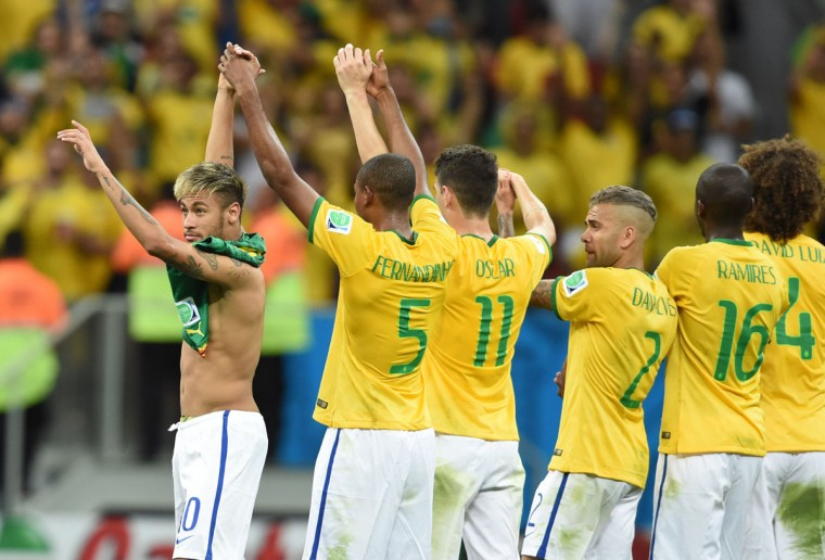 Brazil forward Neymar (left) celebrates as he leaves the pitch with teammates at the end of a Group A football match at the Mane Garrincha National Stadium in Brasilia during the 2014 FIFA World Cup on June 23, 2014. (FRANCOIS XAVIER MARIT/AFP/Getty Images)