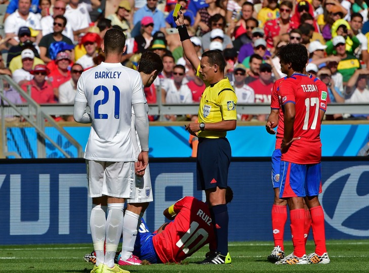 England midfielder Adam Lallana (second left) is given the yellow card after a tackle on Costa Rica forward Bryan Ruiz (below) during a Group D match at the Mineirao Stadium in Belo Horizonte during the 2014 FIFA World Cup on June 24, 2014. (RONALDO SCHEMIDT/AFP/Getty Images)