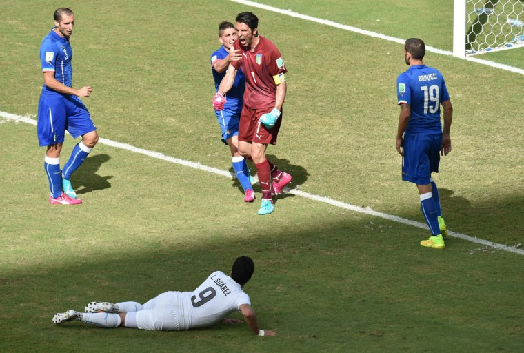Italy goalkeeper and captain Gianluigi Buffon (center) reacts after saving a shot by Uruguay's forward Luis Suarez (bottom) during a Group D football match between Italy and Uruguay at the Dunas Arena in Natal during the 2014 FIFA World Cup on June 24, 2014. (YASUYOSHI CHIBA/AFP/Getty Images)