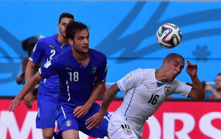 Italy midfielder Marco Parolo (left) and Uruguay defender Maximiliano Pereira vie during the Group D football match between Italy and Uruguay at the Dunas Arena in Natal during the 2014 FIFA World Cup on June 24, 2014. (GIUSEPPE CACACE/AFP/Getty Images)