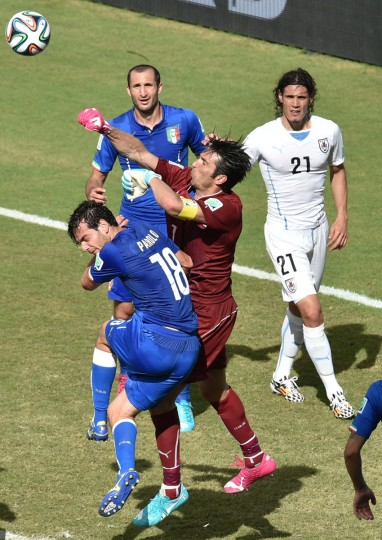 Italy goalkeeper and captain Gianluigi Buffon (center) punches the ball past Italy's midfielder Marco Parolo during a Group D football match between Italy and Uruguay at the Dunas Arena in Natal during the 2014 FIFA World Cup on June 24, 2014. (YASUYOSHI CHIBA/AFP/Getty Images)