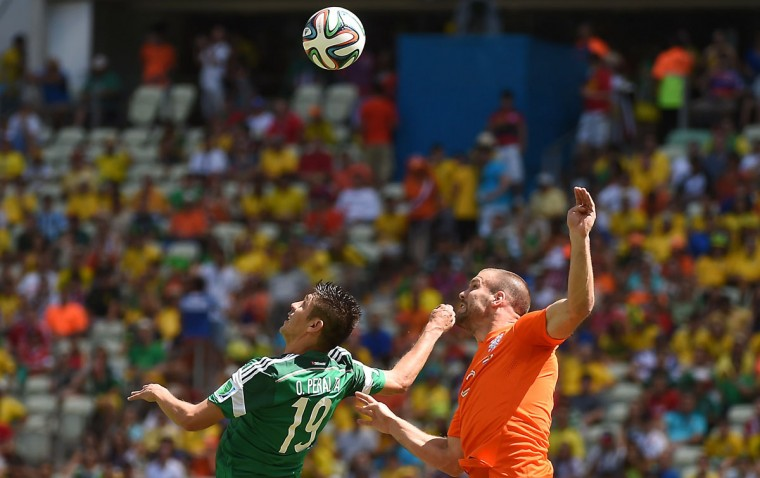 Mexico's forward Oribe Peralta (L) challenges Netherlands' defender Ron Vlaar for the ball during a Round of 16 football match between Netherlands and Mexico at Castelao Stadium in Fortaleza during the 2014 FIFA World Cup on June 29, 2014. (Emmanuel Dunand/AFP/Getty Images)