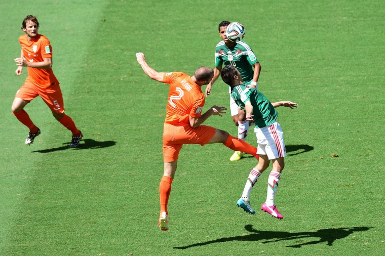 Netherlands' defender Ron Vlaar (C/L) challenges Mexico's forward Oribe Peralta for the ball during a Round of 16 football match between Netherlands and Mexico at Castelao Stadium in Fortaleza during the 2014 FIFA World Cup on June 29, 2014. (Javier Soriano/AFP/Getty Images)