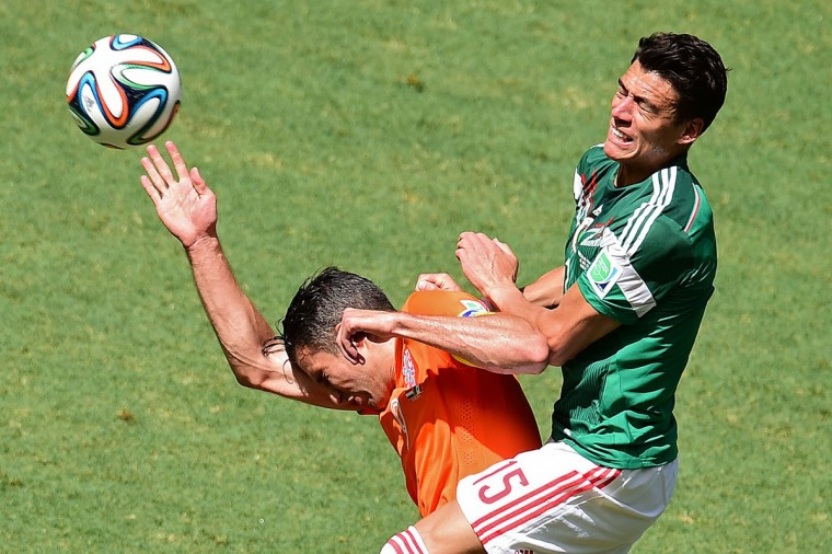 Mexico's defender Hector Moreno (R) challenges Netherlands' forward and captain Robin van Persie during a Round of 16 football match between Netherlands and Mexico at Castelao Stadium in Fortaleza during the 2014 FIFA World Cup on June 29, 2014. (Javier Soriano/AFP/Getty Images)