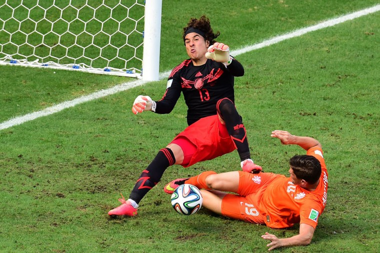 Mexico's goalkeeper Guillermo Ochoa (L) makes a save on a shot by Netherlands' forward Klaas-Jan Huntelaar during a Round of 16 football match between Netherlands and Mexico at Castelao Stadium in Fortaleza during the 2014 FIFA World Cup on June 29, 2014. (Javier Soriano/AFP/Getty Images)