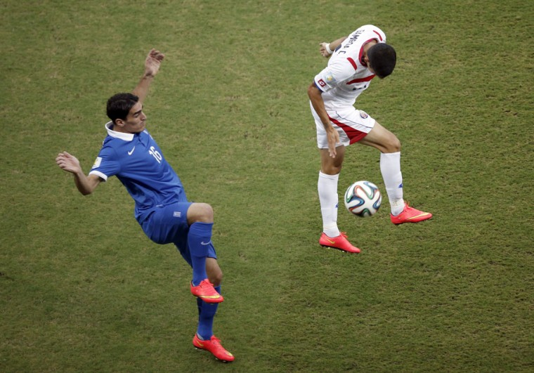 Costa Rica's defender Cristian Gamboa (R) challenges Greece's midfielder Lazaros Christodoulopoulos during the round of 16 football match between Costa Rica and Greece at Pernambuco Arena in Recife during the 2014 FIFA World Cup on June 29, 2014. (Adrian Dennis/AFP/Getty Images)