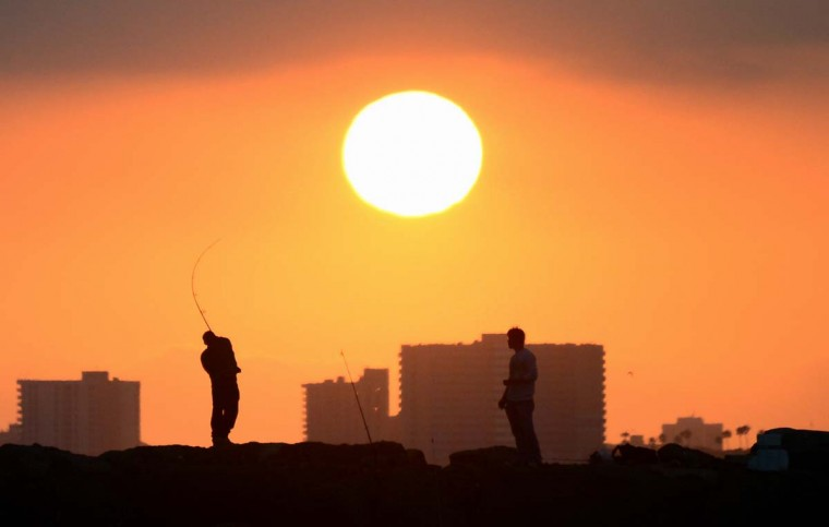"""A fisherman casts his line from the rocks at Seal Beach, California, as the sun prepares to set on June 28, 2014. Summer in California this year is expected to be the hottest and driest on record as nearly one-third of the state experiences """"exceptional"""" drought levels, the highest percentage ever recorded by the Drought Monitor, whch began monitoring in 2000, according to reports last week from the National Climatic Data Center. (Frederic J. Brown/AFP/Getty Images)"""