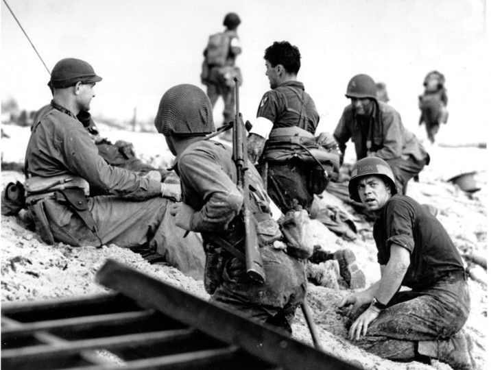 "In this June 6, 1944 file photo, first wave beach battalion ""Ducks"" lay low under the fire of Nazi guns on the beach of southern France on D-Day during World War II. One invader operates a walkie talkie radio directing other landing craft to the safest spots for unloading their parties of fighting men. (AP file photo)"